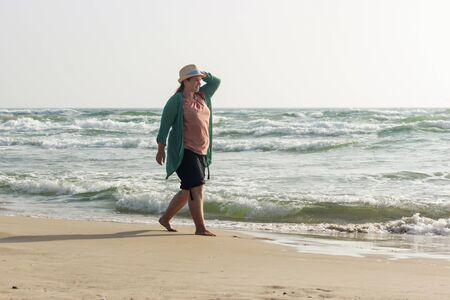 A large girl walks along the edge of the water. A woman enjoys the fresh air and the sea. The girl walks near the sea waves. Zdjęcie Seryjne