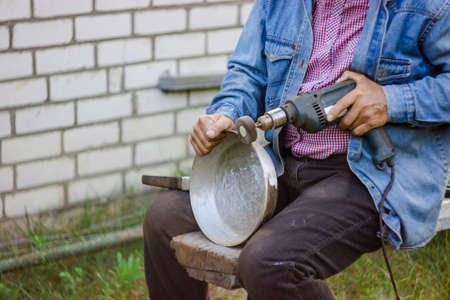 An elderly man cleans the pan mechanically in a personal plot. A man sits with a dirty pan and cleans the burnt fat with a special nozzle.