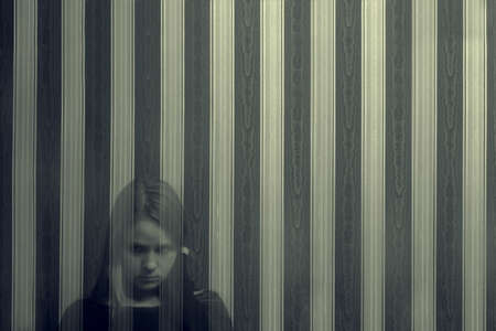 A young translucent ghost girl looks directly at the viewer with a reproach on the background of a striped wall.