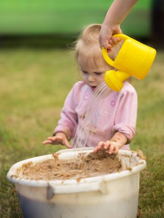 little girl enthusiastically plays with mud in a basin in the courtyard of the house. child pours sand from a watering can.