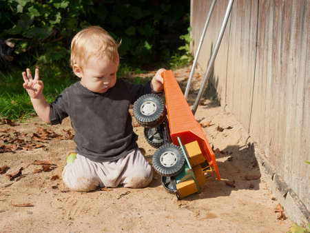 little boy kneels on the sand in the courtyard of the house and plays with a huge toy dump truck. 免版税图像