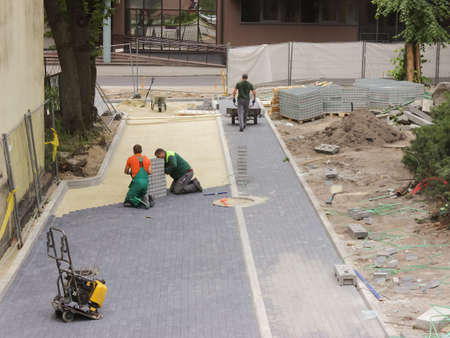 Three working masons are laying paving slabs in a reconstructed city square.