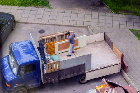Workers load old furniture into the back of a truck to transport