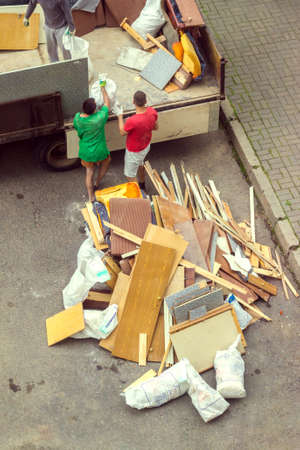 Workers load old furniture into the back of a truck to transport Stock Photo
