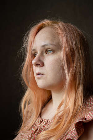 Close-up portrait of a girl with orange hair without makeup and skin retouching.