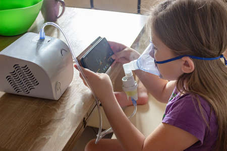 A little girl in a mask does home injections and plays a mobile game so as not to get bored. The use of a home compressor nebulizer.