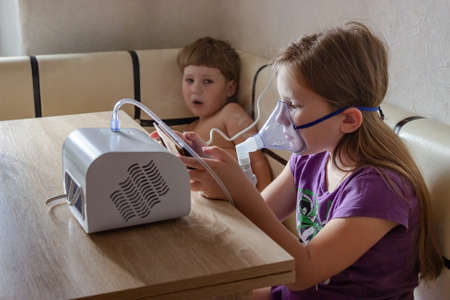 Two small children take turns taking inhalation for a sore throat at home