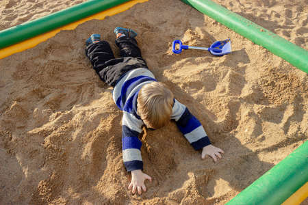 The kid is lying on his stomach in the sand in the city playground. 免版税图像