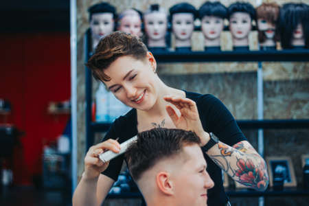 MINSK, BELARUS - OCTOBER 14, 2020: A tattooed woman hairdresser cuts guys hair 新闻类图片