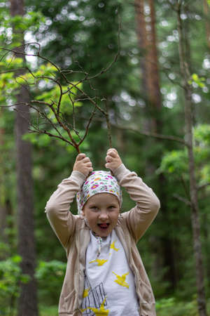 Little girl plays with branches in the forest, fantasizing that these are deer antlers