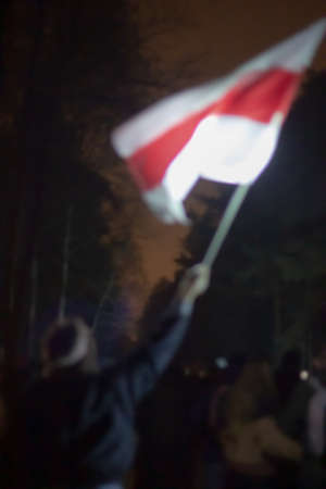 Blurred image of a man with the Belarusian flag in a raised hand.