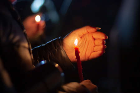 A woman holds a candle in her hand, covering the flame from the wind with her palm, in memory of the dead, killed, dead, deceased, repressed people under the open sky in the night.