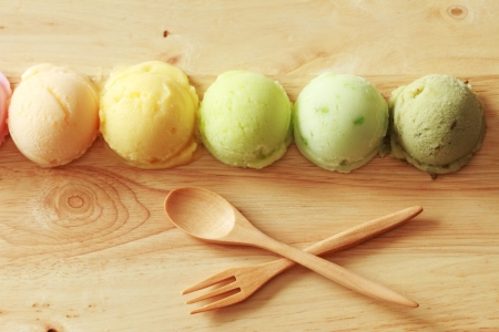 five colorful ice cream scoops in a row with spoon and fork Foto de archivo