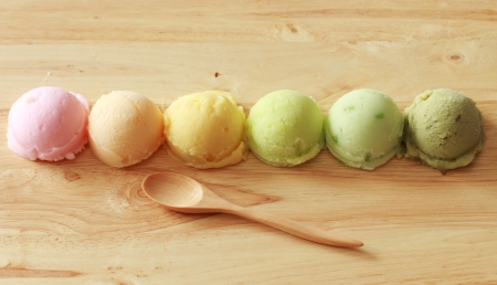 six colorful ice cream scoops in a row from top view with spoon