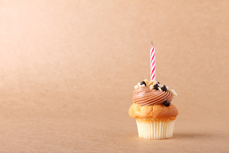 birthday cupcakes: birthday cupcake with candle on plain background