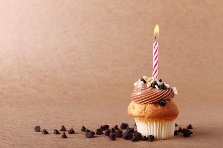 fondo chocolate: magdalena del cumplea�os con la vela en el fondo de chocolate