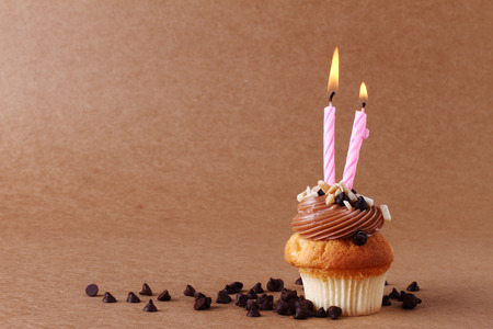 birthday cupcake with candles on chocolate background
