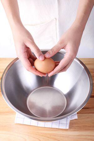 woman prepares egg for baking cake photo