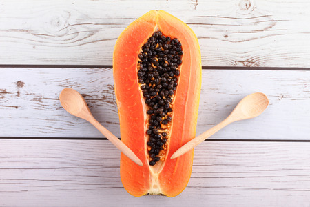 imply: papaya with wooden spoon in boat form