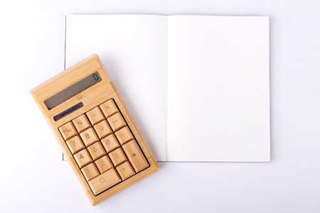 blank notebook with wooden calculator on white background, business concept photo