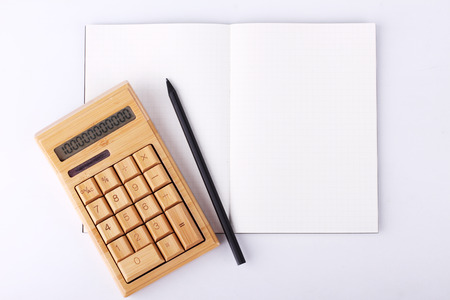 blank notebook with pencil and calculator on white background, business concept photo