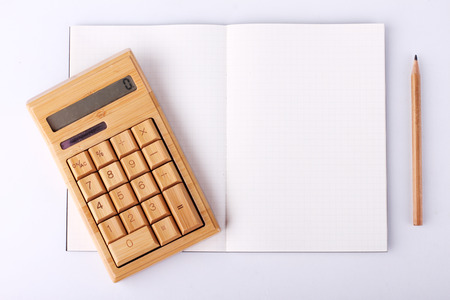 open blank notebook with wooden pencil and calculating machine, business concept photo