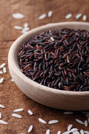 long grain rice,brown rice,in a wooden bowl on wood background Stock Photo