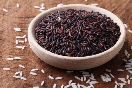 arroz: larga ricebrown grano ricein un cuenco de madera sobre fondo de madera