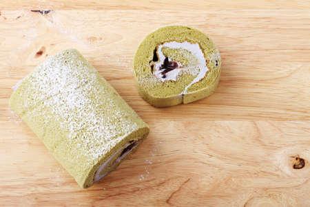 swiss roll: Green Tea Swiss Roll Cake on wooden cutting board