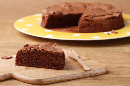 baked homemade chocolate cake with fork on wooden board