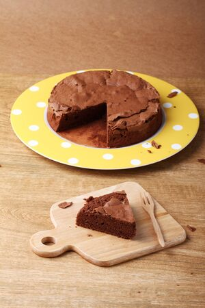 homemade cake: baked homemade chocolate cake with fork on wooden board