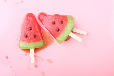 pastel: watermelon shaped ice cream pop lay on pink pastel background