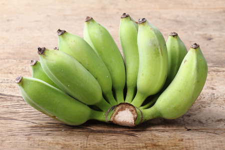 platano maduro: branch of green banana on wooden background Foto de archivo