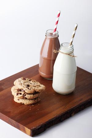 retro flessen melk met gestreepte rietjes en cookies op een houten bord Stockfoto