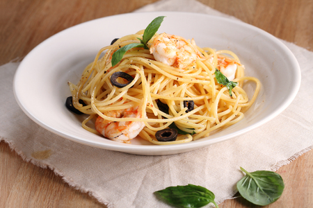 spaghetti pasta with shrimps and sweet basil on wooden table 免版税图像