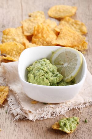 corn chips: guacamole with corn chips on wooden table Stock Photo
