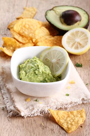 corn chips: guacamole and corn chips with fresh avocado on wooden table
