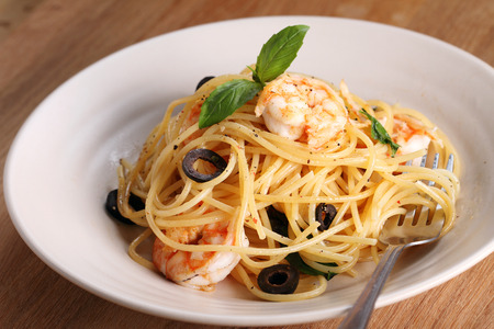 spaghetti pasta with shrimps and sweet basil on wooden table 版權商用圖片