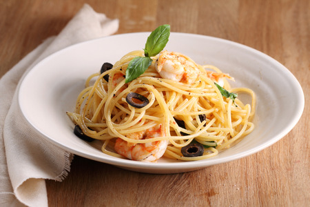 basil: spaghetti pasta with shrimps and sweet basil on wooden table Stock Photo