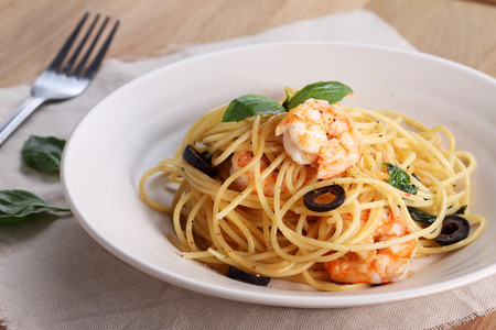 pasta dish: spaghetti pasta with shrimps and sweet basil on wooden table Stock Photo