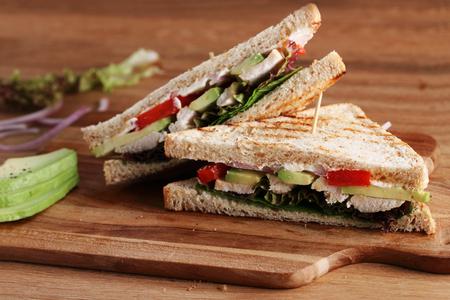 chicken sandwich: Sándwich de pan integral con pollo y aguacate