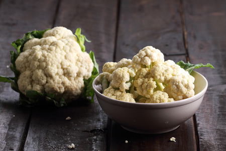 fresh cut cauliflower for cooking in a bowl on rustic wooden background