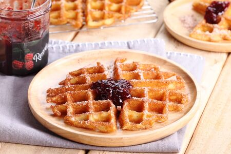 raspberry jelly: waffles cinnamon sugar top with raspberry jelly on wooden background