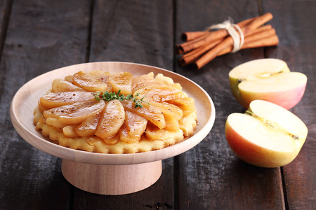 Caramelized apple tart and fresh apples on wooden table Foto de archivo