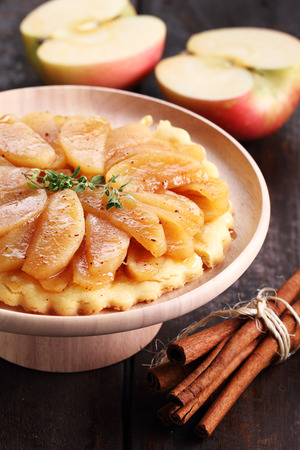 Caramelized apple tart and fresh apples on wooden table Stock Photo