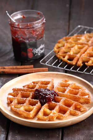 raspberry jelly: waffles cinnamon sugar top with raspberry jelly on rustic wooden background