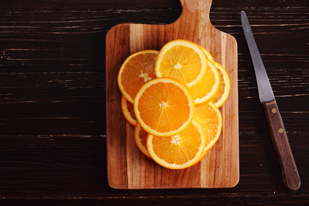 sliced fresh oranges on wooden cutting board with knife
