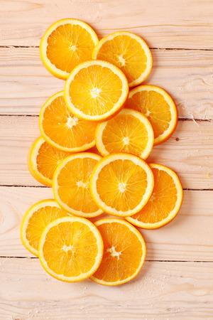 sliced fresh oranges arranged in shape on wooden background
