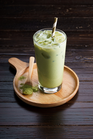 japanese green tea: glass of iced green tea latte on wooden background