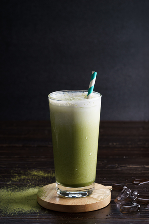glass of iced green tea latte on wooden background